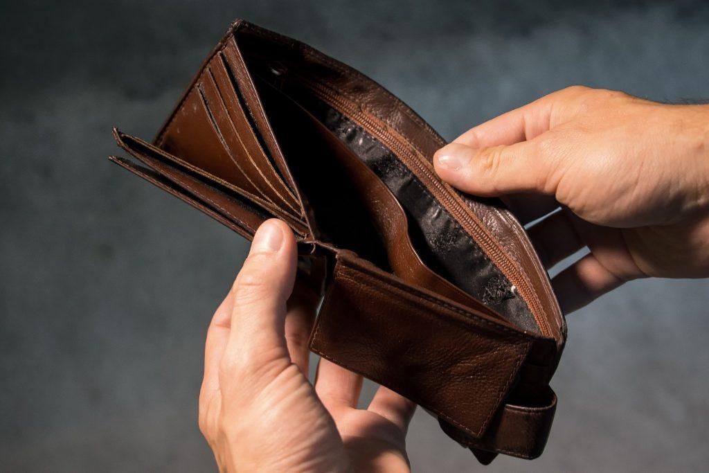 Das Bild zeigt zwei Hände, die einen leeren Geldbeutel in der Hand halten (Schulden).